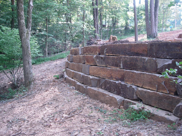 Ledge rock retaining wall by Aching Acres Landscaping for erosion control